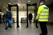 Police using a portable metal detectors to check passengers leaving the London Underground for illegal weapons - Duncan Phillips - ,2000s,2006,adult,adults,checkpoint,CLJ,CLJ crime law,commute,commuter,COMMUTERS,COMMUTING,crime,crime prevention,detector,detectors,door-type,gun,guns,illegal,journey,journeys,knife,knives,leaving,lo