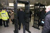 Police using a portable metal detectors to check passengers leaving the London Underground for illegal weapons - Duncan Phillips - 2000s,2006,adult,adults,checkpoint,CLJ,CLJ crime law,commute,commuter,COMMUTERS,COMMUTING,crime,crime prevention,detector,detectors,door-type,gun,guns,illegal,journey,journeys,knife,knives,leaving,lon