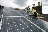 Contractors fixing solar panels to the roof of a terraced house, Barnet, London - Duncan Phillips - ,2010s,2011,cities,city,domestic,EBF,Economic,Economy,ELECTRICAL,electricity,employee,employees,Employment,energy,energy supply,eni,environment,Environmental Issues,fitter,fitters,fitting,fixing,heigh