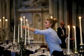 Hospitality worker lighting candles for a formal function, London. - Duncan Phillips - 2010s,2015,candle,candles,candles candle,cities,city,dinner,dinners,EARNINGS,EBF Economy,employee,employees,Employment,EQUALITY,europeregi,Hospitality,hotel hotels,Income,INCOMES,inequality,job,jobs,L