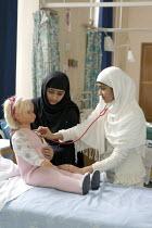 Student Nurses studying paediatric care, in London. - Duncan Phillips - 2000s,2005,BAME,BAMEs,bed,beds,BME,bmes,care,cities,city,diversity,doll,dolls,dress,edu,educate,educating,education,educational,ethnic,ethnicity,FEMALE,hajib,hajib scarf,hajibs,hea,headscarf,health,HE