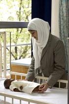 Student Nurse studying paediatric care, in London. - Duncan Phillips - 2000s,2005,BAME,BAMEs,bed,beds,BME,bmes,care,cities,city,diversity,doll,dolls,dress,edu,educate,educating,education,educational,ethnic,ethnicity,FEMALE,hajib,hajib scarf,hajibs,hea,headscarf,health,HE