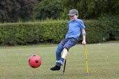 Child with broken leg in plaster playing football - Duncan Phillips - ,2000s,2009,ball,balls,bone,bones,boy,boys,broken,broken leg,child,CHILDHOOD,children,Council Services,Council Services,crutch,crutches,exercise,exercises,exercising,football,game,games,hea,health,inj