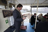 A businessman reading the financial Times on the way to work in the city. Commuters on board the Henley (1895) which runs a river boat service daily from Putney to Blackfriers. The servive is to be re... - Duncan Phillips - ,2010s,2013,adult,adults,boat,boats,businessman,BUSINESSMEN,cities,city,commute,commuter,commuters,commuting,EBF,Economic,Economy,from work,journey,journey to,journeys,lfl,LIFE,lifestyle,London,man,ma