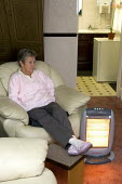 Elderly couple at home, using portable heaters to keep warm because their rented house has no central heating. - Duncan Phillips - 22-03-2006