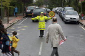 School Lollipop Lady stopping traffic so pedestrians can cross the road. London. - Duncan Phillips - 29-06-2007