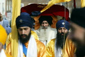 Sikh worshipers at the opening of the new gurdwara Temple in Southall. Worshippers carried a Copy of the Sikh Scriptures, the Guru Granth Sahib, on a Carpet of petals from the old temple to the new. - Duncan Phillips - 2000s,2003,asian,ASIANS,BAME,BAMEs,black,BME,bmes,ceremonies,ceremony,diversity,ethnic,ethnicity,faith,festival,FESTIVALS,god,gudwara,gurdwara,Gurdwara Sri Singh Sabha temple,guru,inclusive,male,men,m