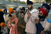 Sikh worshipers at the opening of the new Gurdwara Temple in Southall, the largest sikh temple in Europe. - Duncan Phillips - ,2000s,2003,and,asian,ASIANS,BAME,BAMEs,black,BME,bmes,ceremonies,ceremony,congregation,Crowd,diversity,ethnic,ethnicity,faith,female,god,gudwara,Gurdwara,Gurdwara Sri Singh Sabha temple,guru,inclusiv