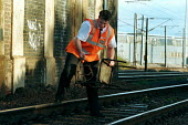 Railway worker on anti vandalism patrol removes debris thrown onto the tracks. This type of vandalism increases during school holiday periods so a dedicated team patrol the tracks to prevent and clear... - Duncan Phillips - 1990s,1999,adult,adults,anti social behavior,anti social behaviour,anti socialanti social behavior,antisocial,antisocial behaviour,antisocialvandalise,antisocialvandalize,CLJ crime law,employee,employ