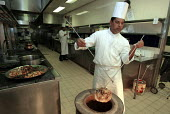 Curry Chef taking part in the Curry Chef 2003 competition. Removing a hot nan bread from a tandoori oven. - Duncan Phillips - 28-10-2003