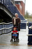 Grandmother pushing a buggy down access ramp with Grandson whilst parents are at work. - Duncan Phillips - 2000s,2004,access,adult,adults,boy,boys,bridge,buggy,care,carer,carers,child,childcare,CHILDHOOD,CHILDMINDING,children,cities,city,early years,families,FAMILY,FEMALE,grandmother,grandmothers,GRANDPARE