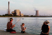 Family fishing on harbour wall in the shadow of industrial plant, Lake Michigan. USA. - Duncan Phillips - 2000s,2003,America,American,americans,beach,BEACHES,capitalism,capitalist,Climate Change,COAST,coastal,coasts,dock,docks,dusk,ebf,Economic,economy,eni,environment,environmental degradation,environment