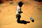 Child walking with homemade toy and bottle. Zimbabwe - Duncan Phillips - 1990s,1997,africa,child,CHILDHOOD,children,EQUALITY,excluded,exclusion,HARDSHIP,impoverished,impoverishment,INEQUALITY,juvenile,juveniles,kid,kids,Marginalised,people,play,playing,POOR,poverty,precari