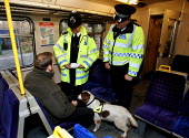 British Transport Police Officers using a drugs dog to Patrol the North London Line. suspect posed by model - Duncan Phillips - ,2000s,2004,adult,adults,animal,animals,canine,CLJ crime law,crime,dog,dogs,drug,drugs,evidence,FEMALE,London,looking,MATURE,metropolitan police service,model,models,network,Officer,officers,packet,Pa