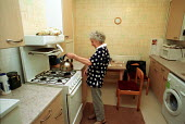 Alice Snoddy Making Tea in her Flat, Lansbury Estate, Tower Hamlets. She was one of the First residents of the 1951 Festival of Britain showpiece housing estate. - Duncan Phillips - 26-01-2005