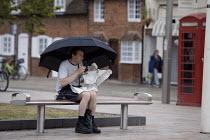A man eating a bag of fish and chips under an umbrella in the rain. Tourism, The British Summer, Bancroft Gardens Stratford-upon-Avon - Emilio Villano-Harris - 04-08-2011