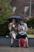 A couple eating ice cream under an umbrella in the rain. Tourism, The British Summer, Bancroft Gardens Stratford-upon-Avon - Emilio Villano-Harris - 2010s,2011,adult,adults,CLIMATE,conditions,confectionery,consumer,consumers,couple,COUPLES,customer,customers,day out,Day Trip,eat,eating,FEMALE,food,FOODS,holiday,holiday maker,holiday makers,holiday