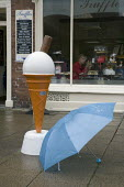 Giant plastic promotional 99 Ice cream cone outside an ice cream shop with an umbrella in the rain. Tourism, The British Summer, Stratford-upon-Avon - Emilio Villano-Harris - 2010s,2011,CLIMATE,conditions,confectionery,day out,Day Trip,eat,eating,EBF,Economic,Economy,food,FOODS,holiday,holiday maker,holiday makers,holidaymaker,holidaymakers,holidays,Leisure,LFL,LIFE,outsid