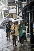 Elderly women walking in the rain past restaurants under an umbrella. Tourism, The British Summer, Stratford-upon-Avon - Emilio Villano-Harris - 2010s,2011,adult,adults,age,ageing population,CLIMATE,conditions,day out,Day Trip,elderly,FEMALE,holiday,holiday maker,holiday makers,holidaymaker,holidaymakers,holidays,Leisure,LFL,LIFE,MATURE,OAP,OA