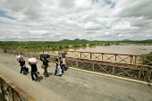 The main border crossing between Zimbawe and South Africa is Beitbridge over Limpopo River. Because of the situation in Zimbabwe a lot of people flee the country over this bridge. Some work carrying g... - Felipe Trueba - 2000s,2007,Africa,border,borders,bridge,carries,carry,carrying,cross,crosses,crossing,Diaspora,displaced,EBF economy,EQUALITY,excluded,exclusion,exodus,FEMALE,flee,fleeing,foreign,foreigner,foreigners