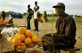 Bulawayo, Zimbabwe. A man sells fruit in a small stall in a road crossing in the outskirts of Bulawayo. Zimbabwe faces an economic chrisis. Food supplies are scarce. - Felipe Trueba - 2000s,2007,bought,buy,buyer,buyers,buying,commodities,commodity,consumer,consumers,cross,crosses,crossing,customer,customers,EBF economy,Food,FOODS,fruit,fruit fruits,FRUITS,goods,groceries,grocery,hi