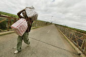 The main border crossing between Zimbawe and South Africa is Beitbridge over Lupopo river. Because of the situation in Zimbabwe a lot of people flee the country over this bridge. Some work carrying go... - Felipe Trueba - 2000s,2007,Africa,border,border borders,border control,border controls,border jumper,border jumpers,borders,bridge,carries,carry,carry carrying,carrying,cross,cross crossing,crosses,crossing,Diaspora,