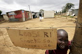 A child smiles at the camera behind a sweets shop sign in a neighbourhood in the outskirts of Johannesburg, South Africa. A large number of Zimbabweans live in these area. - Felipe Trueba - 28-11-2007