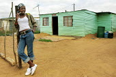 Girl outside her house in a neighbourhood outside Johannesburg that has a large number of Zimbabwean people living there. South Africa. - Felipe Trueba - 2000s,2007,adolescence,adolescent,adolescents,african,africans,Diaspora,EBF economy,EQUALITY,excluded,exclusion,FEMALE,foreign,foreigner,foreigners,HARDSHIP,home,homes,house,houses,housing,hut,huts,im