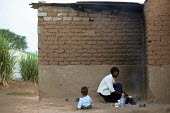 A women prepares some food for her child outside his home in the high density area of Epworth in the outskirts of Harare Zimbabwe. Power and water cuts are very common and people have to light fires i... - Felipe Trueba - 2000s,2007,adult,adults,african,africans,babies,baby,boy,boys,capital,child,CHILDHOOD,children,clearance,clearances,CLEARENCE,cuts,displaced,displacement,EARLY YEARS,ELECTRICAL,electricity,EQUALITY,ex