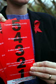 Campaigner with AIDS leaflets and AIDS ribbon on jacket lapel. World AIDS day 1st December 2002 - Geoff Crawford - 2000s,2002,Acquired immune,AIDS,campaign,campaigners,campaigning,CAMPAIGNS,condom,condoms,Contraception,Contraceptive,Contraceptives,deficiency syndrome,disease,diseases,education,equal,HEA health,hea