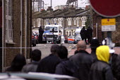 A crowd observes Police marksmen at an armed stand off at Graham Mansions, Hackney, London. - Geoff Crawford - 27-12-2002