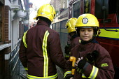 Female Firefighter takes a break from duty at a flat under siege in Hackney, east London January 9, 2003. - Geoff Crawford - 2000s,2003,adult,adults,BAME,BAMEs,black,BME,bmes,break,cities,city,CLJ crime law,cultural,diversity,ethnic,ethnicity,FEMALE,fire,fire brigade,Fire Engine,firefighter,firefighters,fireman,firemen,fire