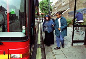 Care worker assists a disabled client at the number 18 bus stop, London. - Geoff Crawford - 24-10-2001