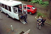 Care workers assist clients boarding the minibus at a day care centre in London - Geoff Crawford - 24-10-2001
