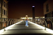 Blurry pedestrian crossing the Millennium Bridge at night with the Tate Gallery in the background. - Geoff Crawford - 11-01-2003