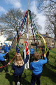Children of Long Preston Primary School in North Yorkshire practise the maypole dance for the May Day celebrations. - Geoff Crawford - 1st,2000s,2003,ACE arts culture,child,CHILDHOOD,children,dance,DANCER,DANCERS,DANCING,EDU education,female,females,festivities,festivity,first,funny,GIRL,GIRLS,green,Humor,HUMOROUS,HUMOUR,joking,jumpi