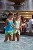 Two young girls enjoy the cooling fountains in Trafalgar Square, London. - Geoff Crawford - 2000s,2003,a,adolescence,adolescent,adolescents,August,boy,BOYS,child,CHILDHOOD,children,cities,city,Climate Change,Climatic,cooling,day,eni environmental issues,Extreme,female,females,fountain,founta