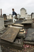 A journalist wanders through damaged gravestones at West Ham Jewish cemetery in Stratford, east London. Over 80 stones were pushed over and the door to the Rothschild family mausoleum was smashed in a... - Geoff Crawford - 16-06-2005