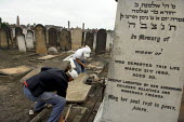 Maintenance staff repair vandalised gravestones at West Ham Jewish cemetery in Stratford, east London. Over 80 stones were pushed over and the door to the Rothschild family mausoleum was smashed in a... - Geoff Crawford - 16-06-2005