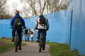 Two cyclistsride next to the blue fence surrounding the 2012 Olympic construction site - Geoff Crawford - 05-03-2008