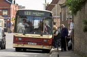 Passengers board the number 128 bus in Snainton village, North Yorkshire - Geoff Crawford - 128,2000s,2005,a,adult,adults,age,ageing population,boarding,bus,bus service,Bus Stop,buses,catching,driver,drivers,driving,elderly,FEMALE,get,getting,house,houses,housing,inaccessible,isolated,isolat