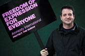 Writer and comedian Mark Thomas poses for pictures with placard for Amnesty International during the Edinburgh Book Festival. - Gerry McCann - 2000s,2006,ace culture,activist,activists,CAMPAIGN,campaigner,campaigners,CAMPAIGNING,CAMPAIGNS,comedian,comedians,comedy,DEMONSTRATING,demonstration,DEMONSTRATIONS,ENTERTAINER,ENTERTAINERS,FUNNY,humo