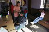 A woman getting her haircut at a hairdressers, in a shanty area in Johannesburg. - Gerry McCann - 24-04-2005