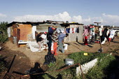 People relaxing at the weekend, in a shanty area in Johannesburg. - Gerry McCann - 2000s,2005,apparel,black,clothing,communities,community,country,countryside,dwelling,dwellings,EQUALITY,excluded,exclusion,FEMALE,friend,friends,friendship,friendships,HARDSHIP,house,houses,housing,hu
