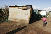 A girl looking into a house, in a shanty area in Johannesburg. - Gerry McCann - 24-04-2005