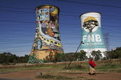 People walking past cooling towers with huge advertisements on them. - Gerry McCann - (FNB),1st,2000s,2005,ACE,advert,ADVERTISED,advertisement,advertisements,advertising,ADVERTISMENT,adverts,bank,banks,cooling,country,countryside,culture,EBF,EBF Economy,Economic,Economy,electric,electr