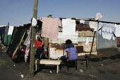Residents relaxing outside, in a shanty area in Johannesburg. - Gerry McCann - 08-05-2005