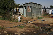 Children playing outside, in a shanty area in Johannesburg, which has a water tap to provide clean water for dozens of families. - Gerry McCann - 08-05-2005