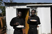 Two brothers having lunch outside their home, in a shanty area in Johannesburg. - Gerry McCann - 08-05-2005