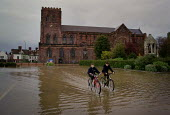 Two boys cycling through the underwater car park of Shrewsbury Abbey, as the River Severn flooded in Shropshire, UK - Paul Herrmann - 2000,2000s,BAD,bicycle,BICYCLES,BICYCLING,Bicyclist,Bicyclists,BIKE,BIKES,BOY,boys,child,children,Climate Change,companions,CYCLE,cycles,cycling,Cyclist,Cyclists,DIA disasters,ENI environmental issues